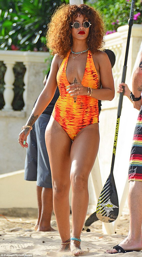 Rihanna Turns Up in an orange flame stripped swim suit, hits the beach in Barbardos