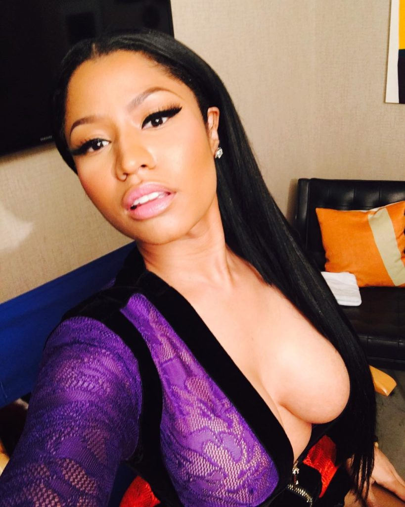 Nicki Minaj Shows off her raunchiness, as she poses in sheer purple and pink dress