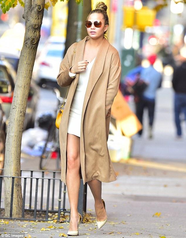 Chrissy Teigen rocks A Beige Coat with Tight White Dress
