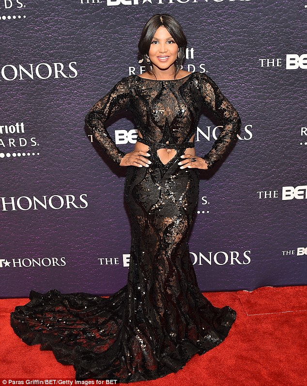 Toni Braxton puts her belly on display in a Black Shiny  ultra-sheer cut-out mermaid gown at BET Honors in Washington, D.C