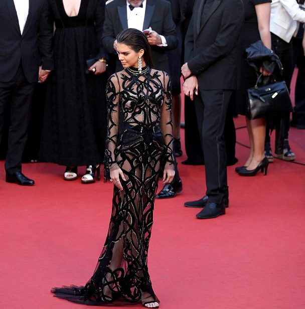 The 20-year-old Supermodel made a show stopping appearance at the 2016 Cannes films Festival current going on today in France.  Kendall made the world stood still as she arrived the red carpet in a black see-through Black Sheer Dress.  The Model accessorized with some long shiny earrings while complementing her dress with sexy black Heeled sandals.
