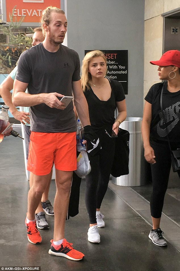 Chloe Grace Moretz dons low black tee with a plunging neckline top and tight leggings to join brother for spin class