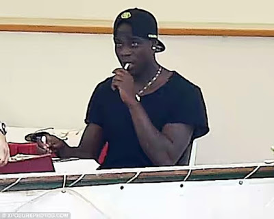 Mario Balotelli enjoys smoking a Cigarette as he enjoys his holiday on a yacht in Italy