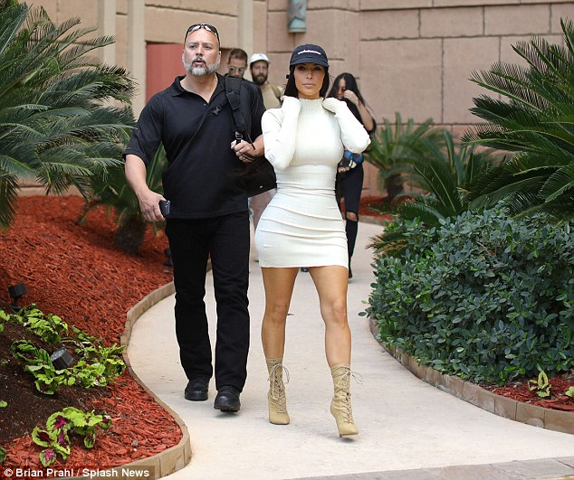 Kim Kardashian shows off her  Bootilicious rear in a form fitting white dress