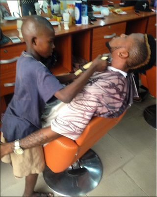 Meet a 10 year old barber Olalekan who makes at least N5,000 daily