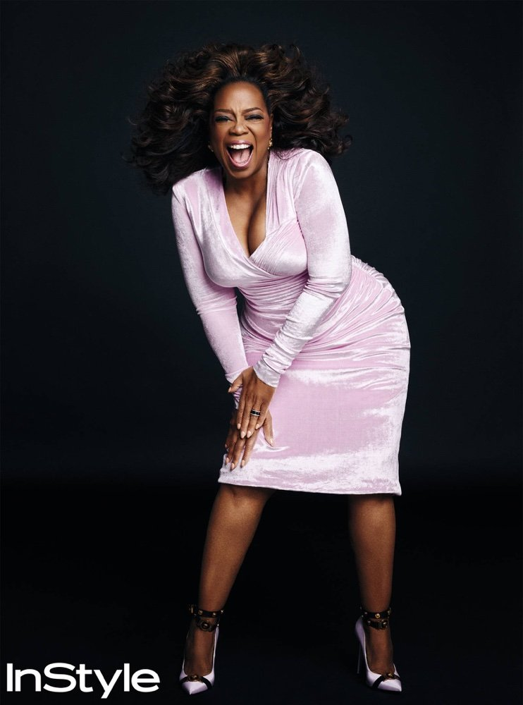 Oprah Winfrey in a Versace dress, earrings, and pumps with a Bulgari ring.