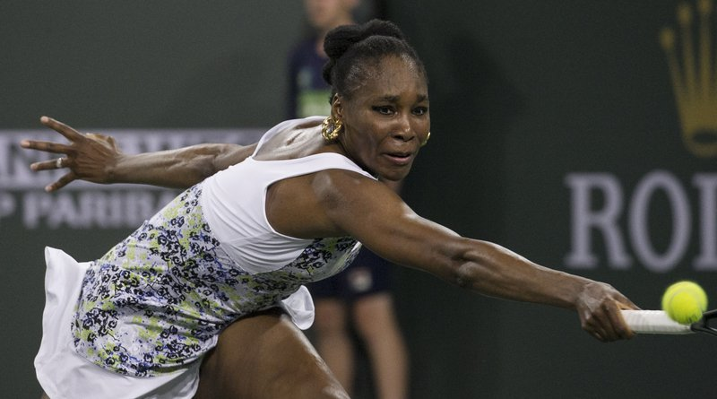 Venus Williams stretches to return a shot to opponent and sister Serena Williams during the third round of the BNP Paribas Open tennis tournament at the Indian Wells Tennis Garden in Indian Wells, Calif., Monday, March 12, 2018. (AP Photo/Crystal Chatham)