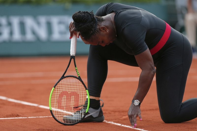 Serena Williams of the U.S. cleans the baseline with her fingers during her second round match of the French Open tennis tournament against Australia's Ashleigh Barty at the Roland Garros stadium in Paris, France, Thursday, May 31, 2018. (AP Photo/Thibault Camus)
