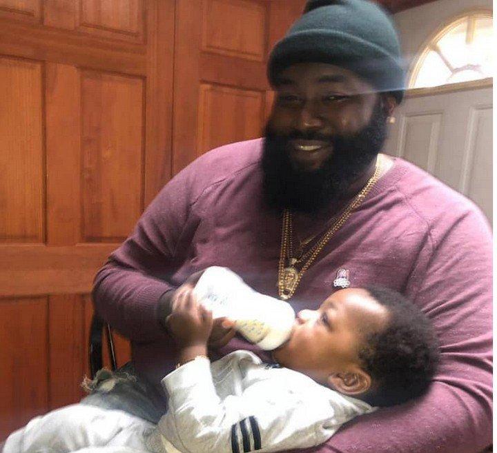 Photos of Davido's Hypeman,Special Spesh Bottle-feeding His Son